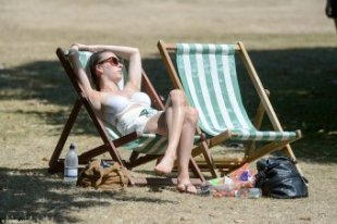 Soaking up the sun: One woman makes the most of the warm weather as she reclines on a deck chair in Hyde Park, London today