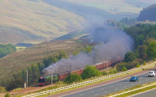 Steam train locomotive next to the M6 motorway in the River Lune Valley, Cumbria
