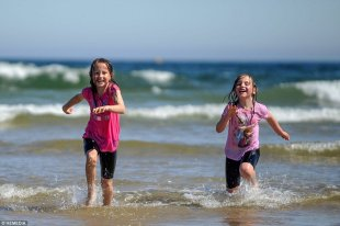 Summer fun: Sisters Sophie Wenman, nine, and Hannah Wenman, seven, are seen playing in the sea on a beach in Lossiemouth, Scotland